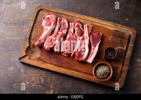 Raw fresh lamb ribs with pepper and cumin on wooden cutting board on dark background - Stock Photo