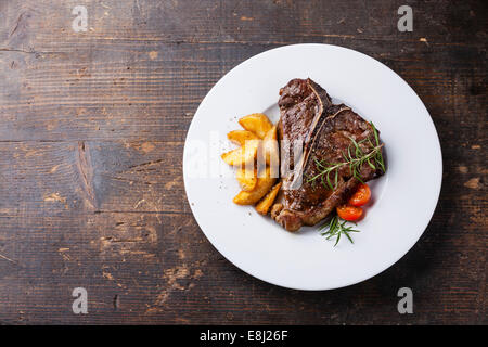 T-Bone Steak with roasted potato wedges on white plate on wooden background - Stock Photo