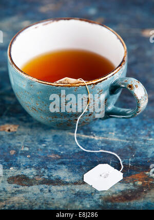 Cup of tea with teabag on blue textured background - Stock Photo