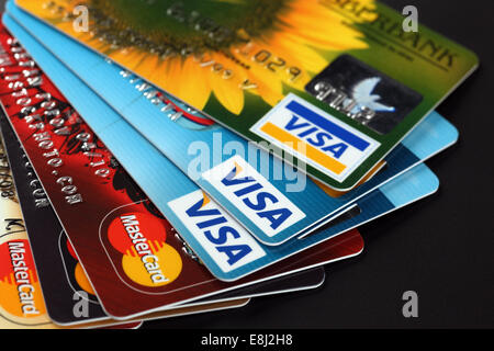 Tambov, Russian Federation - September 11, 2012: Heap of credit cards with Visa and Mastercard logos on black background. - Stock Photo