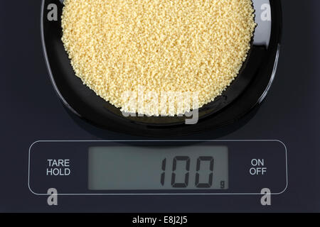 Couscous in a black plate on digital scale displaying 100 gram. - Stock Photo