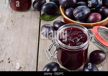 Homemade plum jam and group of plums on old wooden table. Plenty of copyspace. - Stock Photo