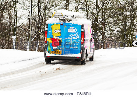 Sky television media van with bart simpson painted on the back door approaching a roundabout in the snow - Stock Photo