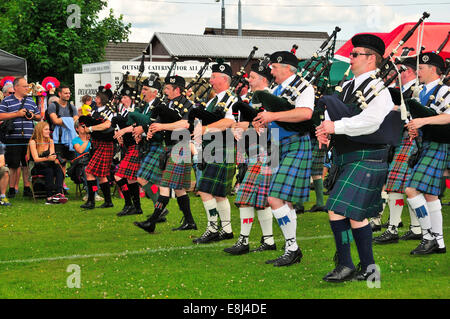 Pipe band marching in unison on the sports ground at the Highland Games, Dufftown, Moray, Highlands, Scotland, United - Stock Photo