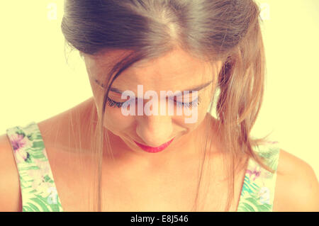 portrait of a young brunette woman looking downwards, with a retro effect - Stock Photo