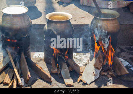 FOOD COOKING IN BRASS POTS OVER OPEN FIRES IN INDIA - Stock Photo