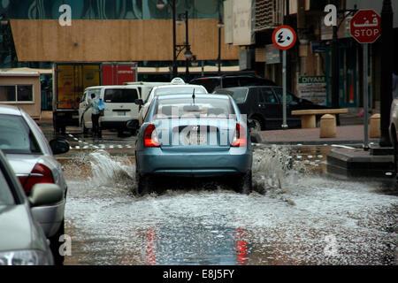 A car drives through the built-up rain water in the streets of Riyadh, Saudi Arabia - Stock Photo