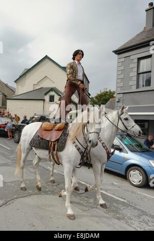 An equestrian riding two Lusitano dressage horses leads the opening procession of the Abersoch Jazz Festival 2014, - Stock Photo