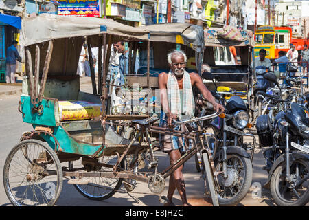 RICKSHAW DRIVER AND AN OLD RICKSHAW AMONG THE MODERN MACHINES IN THE STREETS OF INDIA - Stock Photo