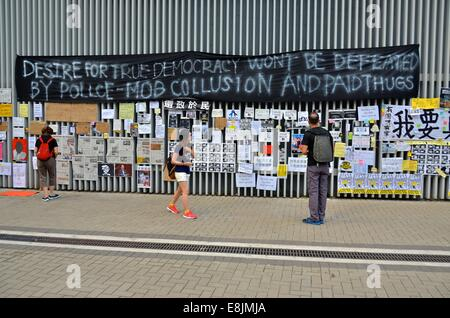 Hong Kong. 9th October, 2014. People reading messages which have been posted on the walls of government buildings - Stock Photo