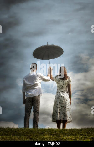 a couple on a meadow with an umbrella - Stock Photo