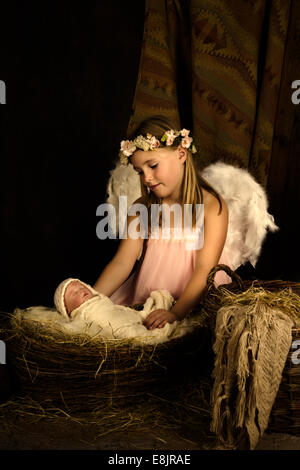 Pink little girl playing an angel in a Christmas nativity scene with a doll - Stock Photo