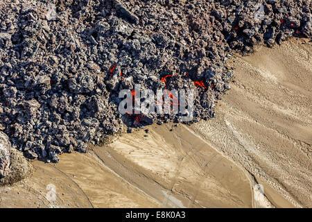 Hot lava creeping by tire tracks. Eruption site at Holuhraun near Bardarbunga Volcano, Iceland. - Stock Photo