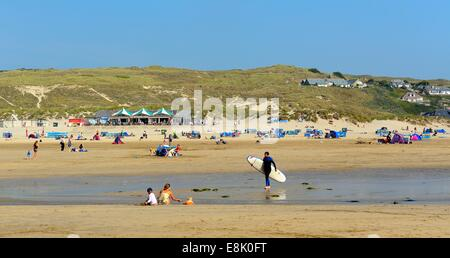 A man carry a surf board on Perranporth Beach Cornwall England uk - Stock Photo
