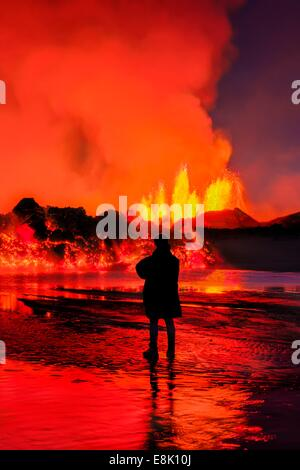 Woman watching the lava flow at the Holuhraun Fissure eruption near the Bardarbunga Volcano, Iceland - Stock Photo