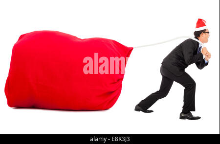 business man carrying a heavy gift sack with christmas hat. isolated on white background - Stock Photo