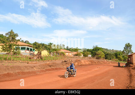 A motorbiker riding the dirt roads in the pure sky of the Fouta Djalon hills of Guinea, West Africa - Stock Photo