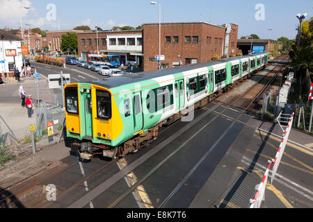 Southern Railway train passing over level crossing, Chichester, West Sussex - Stock Photo
