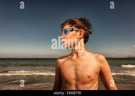 Boy wearing swimming goggles at seaside - Stock Photo
