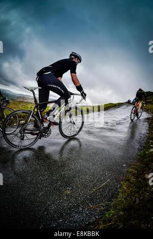 Cyclist climbing 33% gradient on Hardknott Pass, English Lake District, UK. - Stock Photo