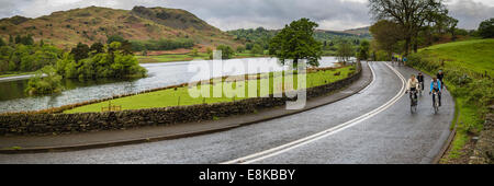 Group of cyclists on the road by Rydal Water, English Lake District, UK. - Stock Photo