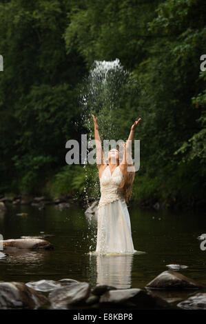 Trash the dress: a 'bride' wearing her wedding dress standing in a river throwing water into the air - Stock Photo
