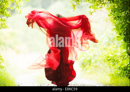 Scarlet woman: rear view of a girl wearing a blood red frock dress in running away woodland countryside - Stock Photo