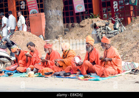 Group of sadhus sat in safron robes & turbans singing holy chants (bhajans mantras) on the Shiva new moon festival - Stock Photo