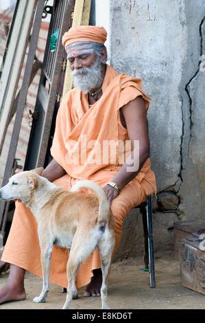 Sadhu in safron robes & turban sat with dog on the pradacshina street around Arunachala sacred mountain Tiruvannamalai - Stock Photo