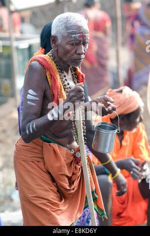 Old blind sadhu seeking alms in safron orange lungi outside Agni (fire) Lingam (Siva) Pradacshina shrine Arunachala - Stock Photo