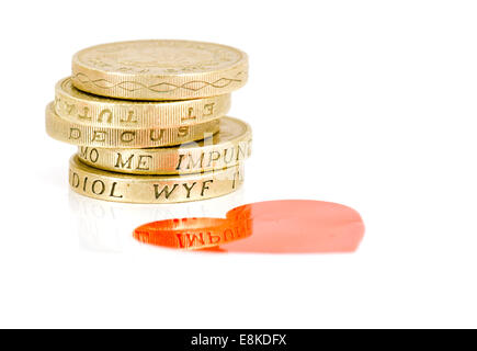 One Pound Coins by a red heart - Stock Photo