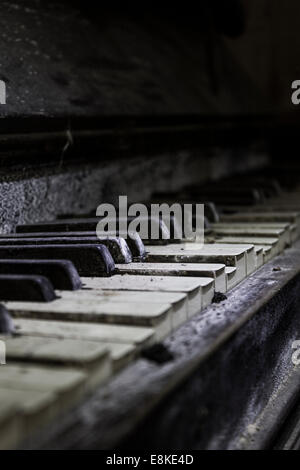Close up of the damaged and broken keys of an old dilapidated piano - Stock Photo