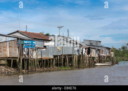 Slums built on stilts over the canals in the Mekong Delta. - Stock Photo