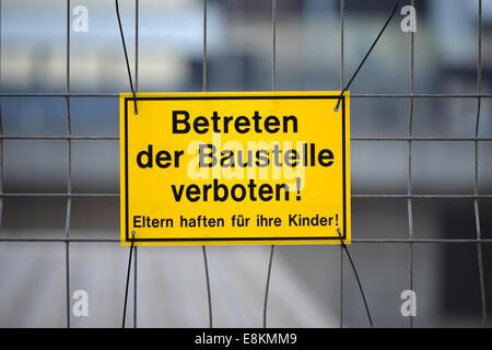 Warning sign 'Betreten der Baustelle verboten! Eltern haften für ihre Kinder!' or 'No Trespassing! Parents responsible - Stock Photo