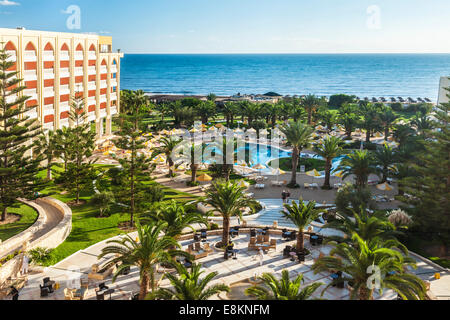View of the poolside area of a five star resort hotel near Port el Kantoui in Tunsia with the Mediterranean sea - Stock Photo