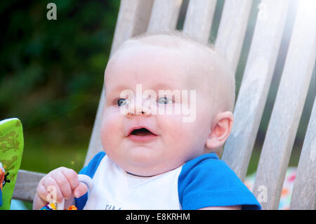 Baby sitting on a garden chair in the garden - Stock Photo
