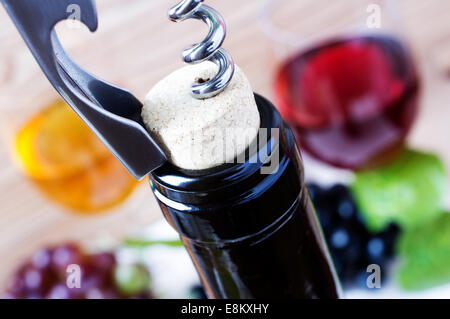 Corkscrew opening a bottle of wine - Stock Photo