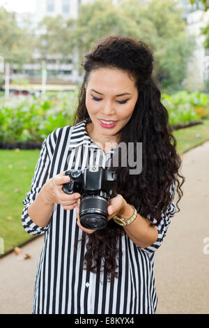 young woman looking through photos on her camera - Stock Photo