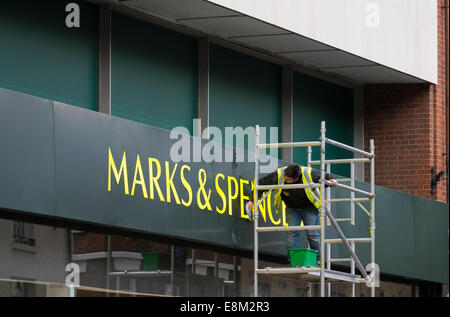 Worker cleaning Marks and Spencer shop sign in Shrewsbury Shropshire England UK - Stock Photo