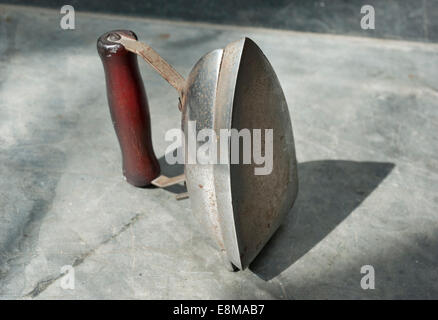 An old battered portable small electric travelling Iron from the 1950s - Stock Photo