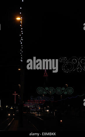 Night portrait, towards purple lights Blackpool Tower, colourful Scrolls above cars, Central Promenade, Blackpool - Stock Photo