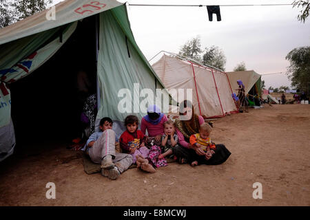 Yazidi women with young children siting amid temporary shelter tents at a refugee camp for displaced people from - Stock Photo