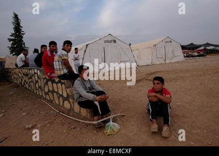 Young Yazidi children siting next to temporary shelter tents donated by UNICEF at a Yazidi refugee camp in the town - Stock Photo