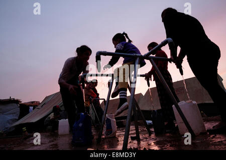 Yazidi women with their children filling drinking water in plastic jerrycans at a refugee camp for displaced people - Stock Photo