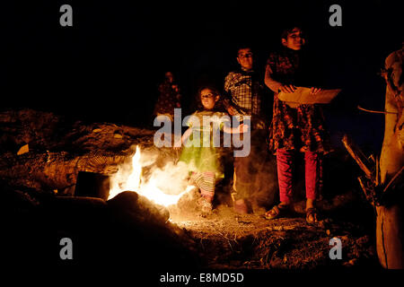 Yazidi children warming themselves around a bonfire at a refugee camp for displaced people from the minority Yazidi - Stock Photo