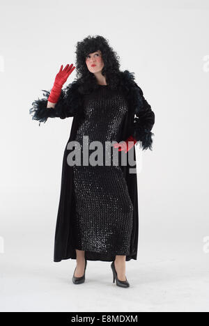 woman in fancy dress, comedy costume as a sassy, party lady in a black dress and wig with red gloves - Stock Photo