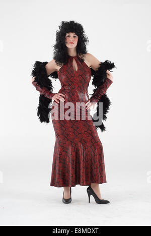 Woman in fancy dress comedy costume in a red snake skin dress, with feather bower and black wig - Stock Photo