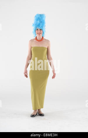 Woman in fancy dress comedy costume in a marge simpson cartoon tv show outfit with blue wig, gold dress and neckless - Stock Photo