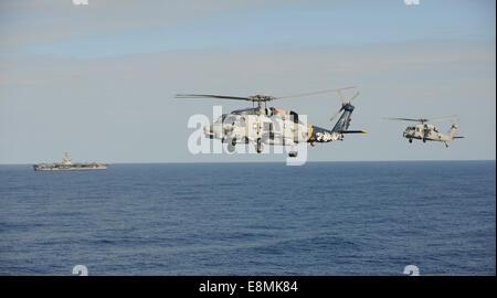 Pacific Ocean, December 2, 2013 - An MH-60R Sea Hawk helicopter, left, and an MH-60S Sea Hawk helicopter fly during - Stock Photo