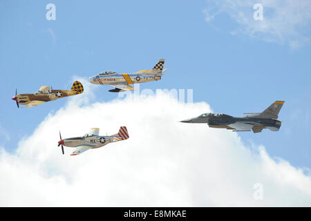 March 2, 2014 - An F-16 Fighting Falcon joins in formation with a P-40 Warhawk (front), P-51 Mustang (bottom), and - Stock Photo
